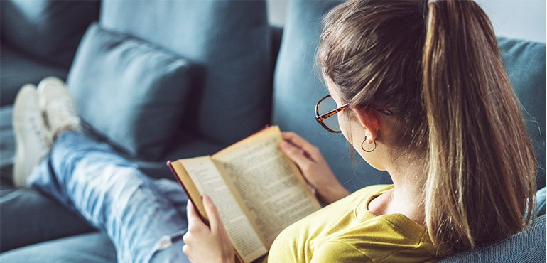 A girl lies on a couch reading.